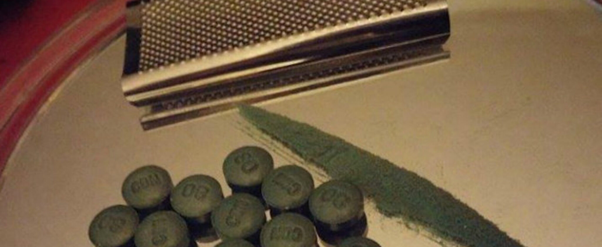 Green W-18 pills and powder spread over a mirror
